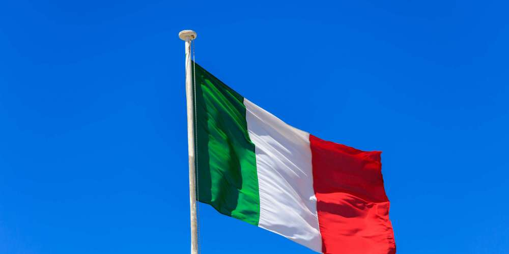 Italy flag. Italian flag on a flagpole waving on a bright blue sky background