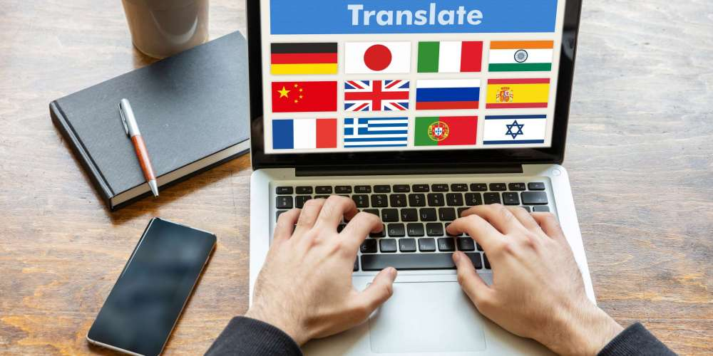 Online translation, foreign languages learning concept. Man working with a computer laptop, translate text on the screen.